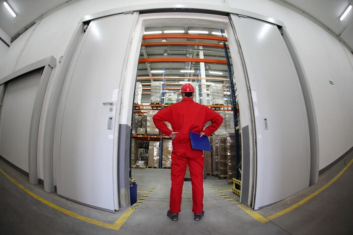 A fish eye view of a worker standing in the doorway of a modern industrial facility.