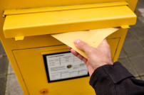 Person wirft Brief in Briefkasten