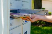 Jemand nimmt Post aus Briefkasten