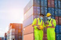 Logistiker mit Maske vor Containern