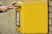 Mann steckt Brief in Briefkasten