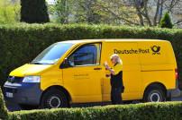 Postbotin an Zustellfahrzeug der Deutschen Post