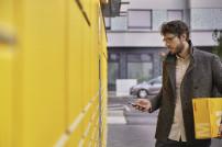 Mann bedient Packstation mit Smartphone