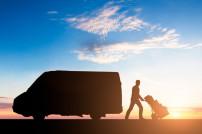 Paketbote vor Transporter im Sonnenuntergang