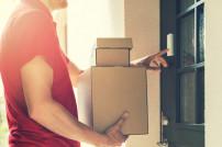 Zusteller mit Paketen klingelt an Haustür