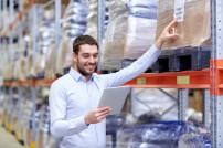 Mann mit Tablet-PC in Logistikzentrum.