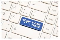 Tastatur mit blauer Taste auf der eine Weltkarte ist und Fair Trade steht